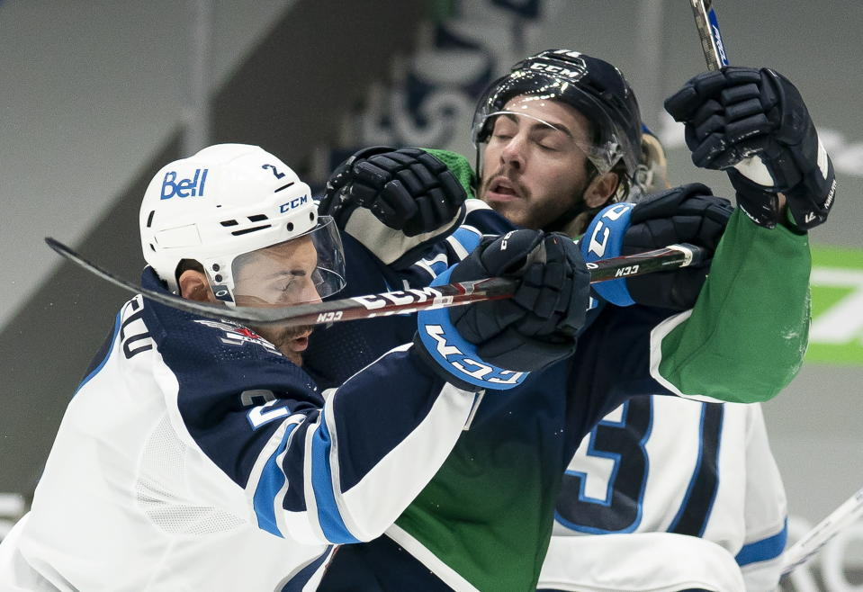 Winnipeg Jets defenseman Dylan DeMelo (2) fights for control of the puck with Vancouver Canucks center Zack MacEwen (71) during second-period NHL hockey game action in Vancouver, British Columbia, Sunday, Feb. 21, 2021. (Jonathan Hayward/The Canadian Press via AP)