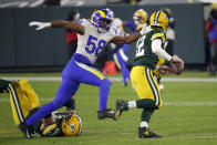 Green Bay Packers quarterback Aaron Rodgers is chased by Los Angeles Rams' Justin Hollins during the second half of an NFL divisional playoff football game Saturday, Jan. 16, 2021, in Green Bay, Wis. (AP Photo/Mike Roemer)