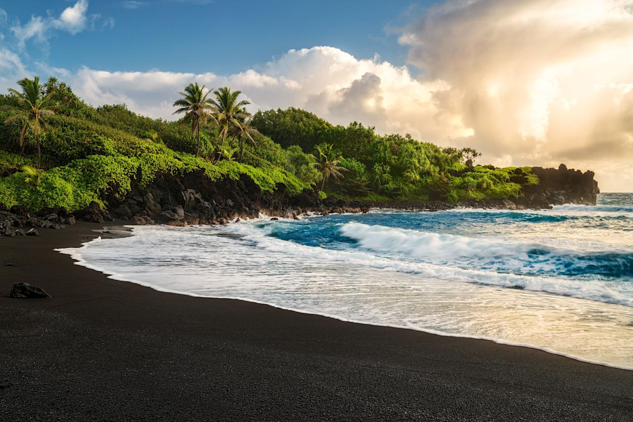 """<p>Just off Maui's renowned Hana Highway, <a href=""""https://dlnr.hawaii.gov/dsp/parks/maui/waianapanapa-state-park/"""" target=""""_blank"""">Wai'anapanapa State Park</a> is home to a seabird colony, sea stacks, arches, and other natural wonders, but its small black sand beach, created by the surf grinding down the lava flow of the Haleakela Volcano, is the prize. Further, the emerald naupaka shrubs lining the beach add a stunning contrast to the dark, dark sands. </p>"""