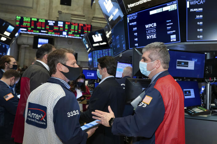 In this photo provided by the New York Stock Exchange, traders Robert Charmak and John Panin, foreground left and right, work on the floor, Friday, March 5, 2021, in New York. Stocks are swerving through another rocky ride Friday, as investors struggle to figure out what an encouraging report on the economy and the recent march higher for bond yields should mean for the market. (Nicole Pereira/New York Stock Exchange via AP)