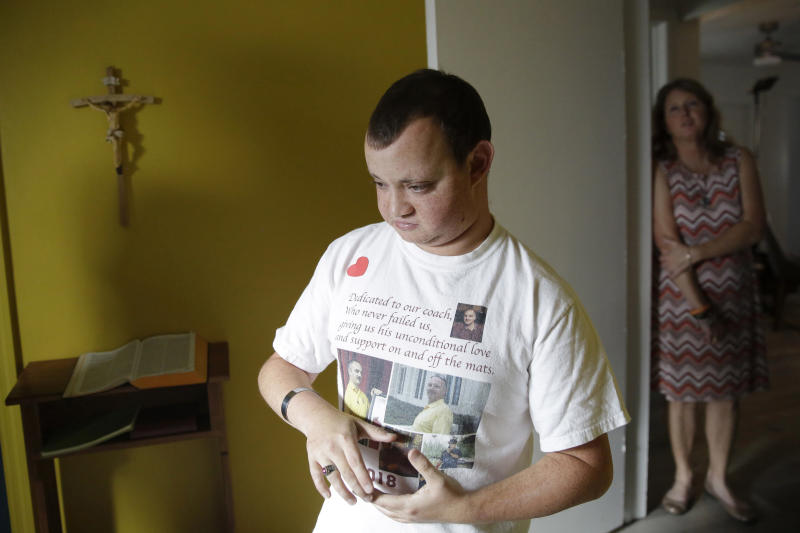 """Corey Hixon, 24, wears a shirt with photographs of his father, Chris Hixon, as his mother, Debbi Hixon, stands in the doorway on Friday, Feb. 14, 2020, in Hollywood, Fla. Chris Hixon was killed in the school shooting on Valentine's Day two years ago at Marjory Stoneman Douglas High School in Parkland, Fla. """"He's still part of our family and i didn't want it to feel like he's not here anymore,"""" she said of the home renovation completed during a whirlwind 10-days for the show """"Military Makeovers."""" (AP Photo/Brynn Anderson)"""