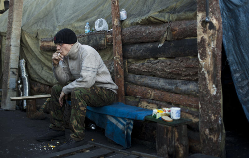A member of a self defense volunteer group smokes a cigarette as he sits outside a tent in Kiev's Independence Square, Ukraine, Tuesday, March 11, 2014. (AP Photo/David Azia)