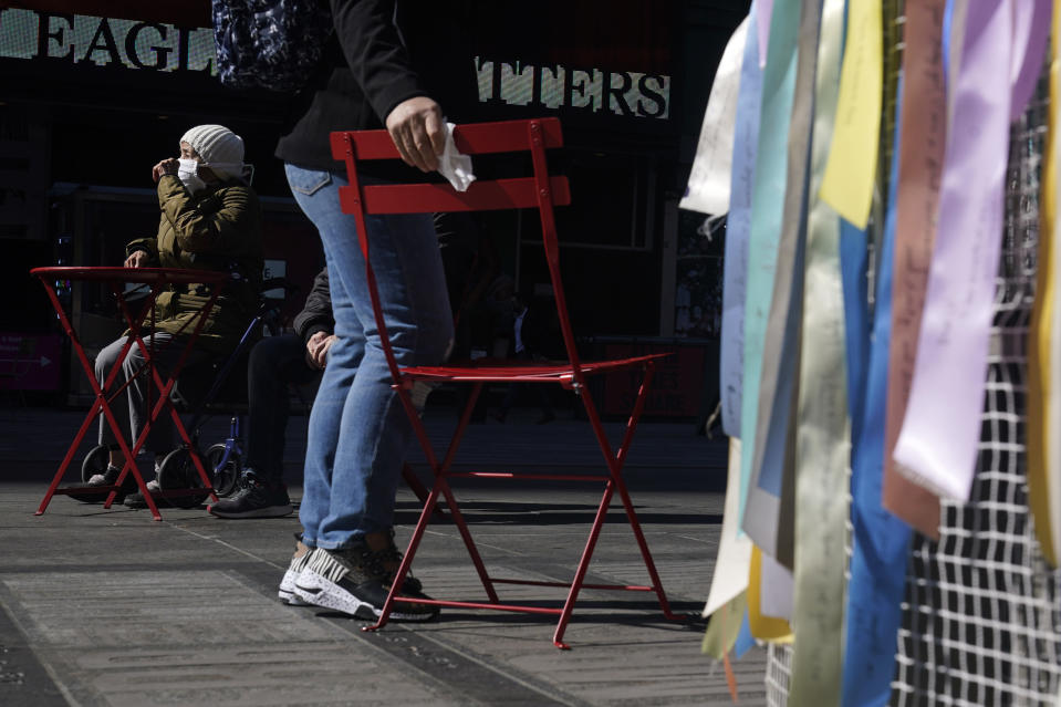 FILE - A woman wipes down chair before sitting on it in Times Square in New York, Wednesday, March 10, 2021. After the virus descended on New York, the only sounds in the streets were wailing ambulance sirens. A year after the pandemic began, the nation's largest metropolis -- with a lifeblood based on round-the-clock hustle and bustle, push and pull -- is adapting and showing new life. (AP Photo/Seth Wenig)