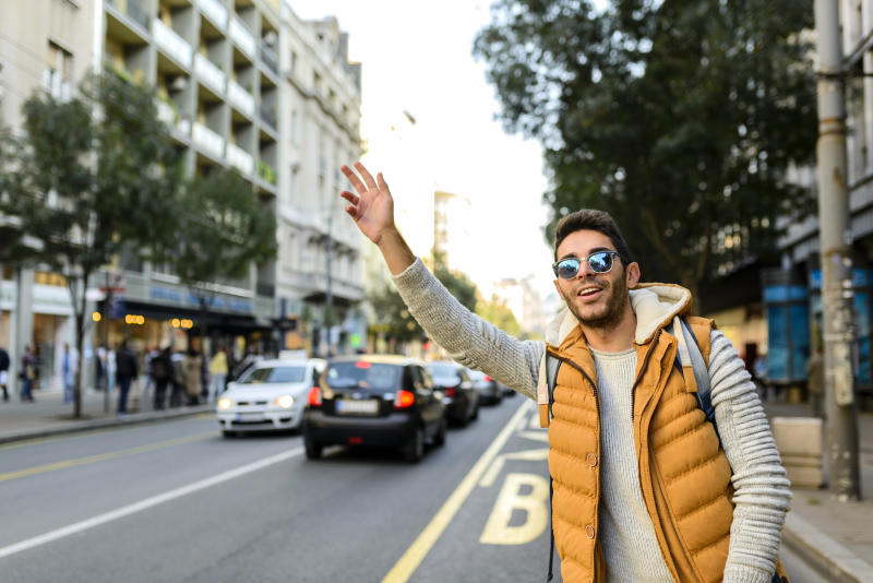 A young man hailing a cab.
