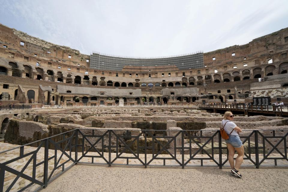 """A visitor poses in front of the newly restored lower level of the Colosseum, during an event for the media, in Rome, Friday, June 25, 2021. After 2-and-1/2 years of work to shore up the Colosseum's underground passages, tourists will be able to go down and wander through part of what what had been the ancient arena's """"backstage."""" (AP Photo/Andrew Medichini)"""