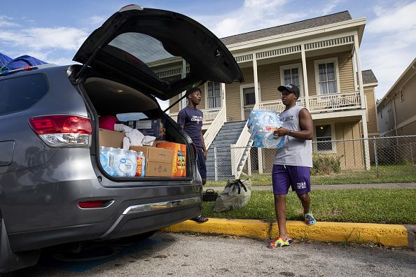 A resident places cases of water in a car while evacuating from a home ahead of Hurricane Laura in Galveston, Texas.
