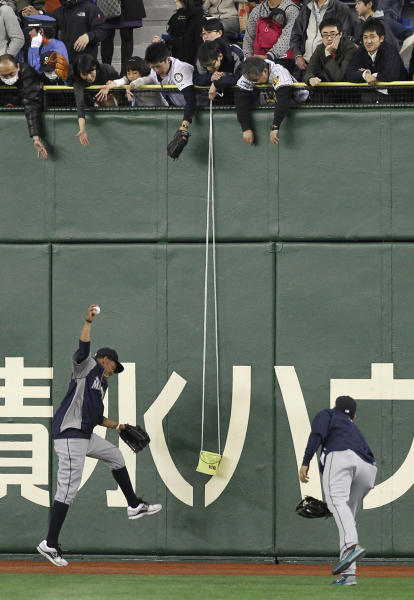 A Japanese baseball fan intends to take advantage of lowering a bucket to collect autographed balls from the Seattle Mariners players before an exhibition baseball game between the Mariners and Japan's Hanshin Tigers at the Tokyo Dome in Tokyo, Sunday, March 25, 2012. The Mariners will meet the Oakland Athletics in their two season-opening baseball games of the major league in Japan, at the Tokyo Dome from Wednesday. (AP Photo/Koji Sasahara)