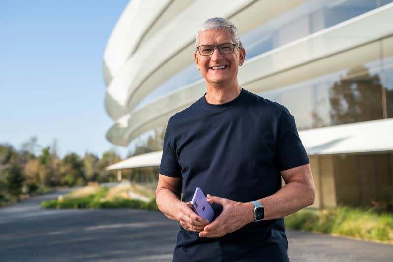 Apple CEO Tim Cook holds an iPhone 12 in a new purple finish