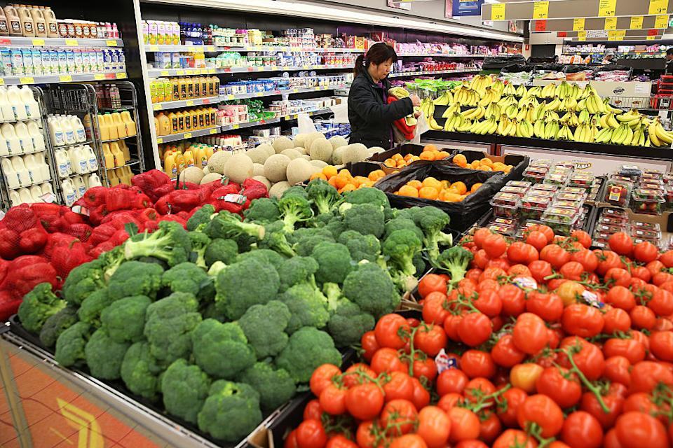 A customer holding a plastic bag and towels stands near fresh produce and fruits at an Aldi Stores Ltd. food store in Sydney, Australia, on Thursday, June 25, 2015.