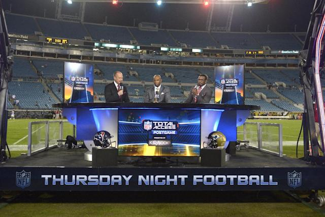 NFL Network commentators Rich Eisen, left, Deion Sanders, center, and Michael Irvin broadcast from the field after an NFL football game between the Jacksonville Jaguars and Houston Texans in Jacksonville, Fla., Thursday, Dec. 5, 2013.(AP Photo/Phelan M. Ebenhack)