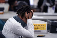 An elections worker rubs his head in the closing hours where absentee ballots were processed at the central counting board, Wednesday, Nov. 4, 2020, in Detroit. (AP Photo/Carlos Osorio)