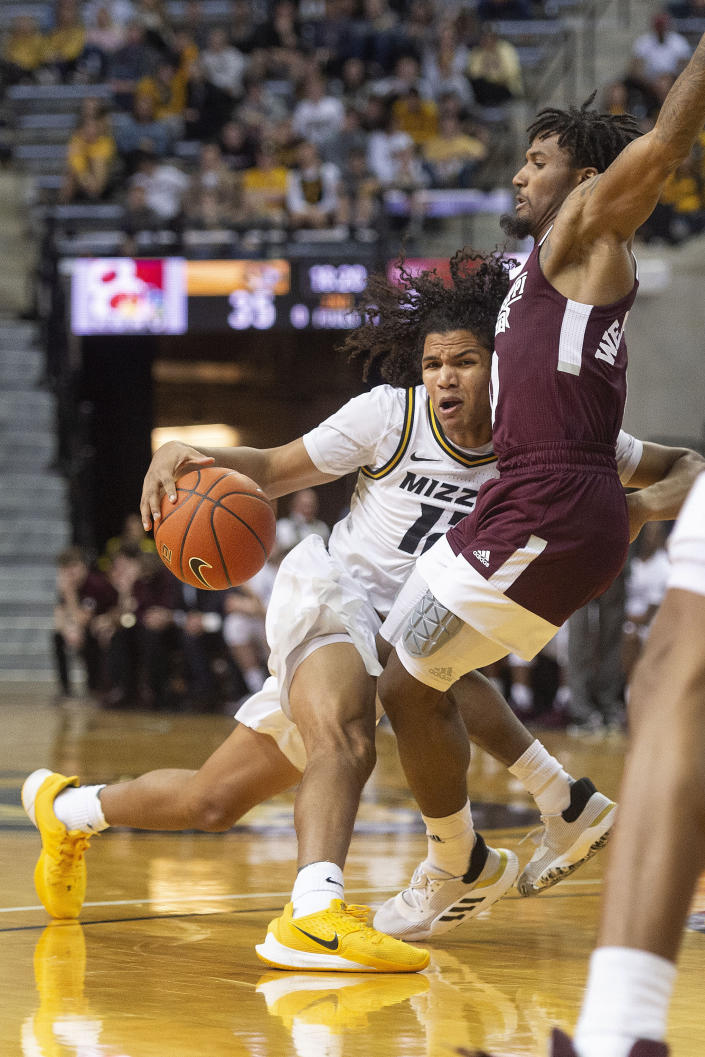 Missouri's Dru Smith, left, dribbles into Mississippi State's Nick Weatherspoon, right, during the second half of an NCAA college basketball game Saturday, Feb. 29, 2020, in Columbia, Mo. Mississippi State won 67-63. (AP Photo/L.G. Patterson)