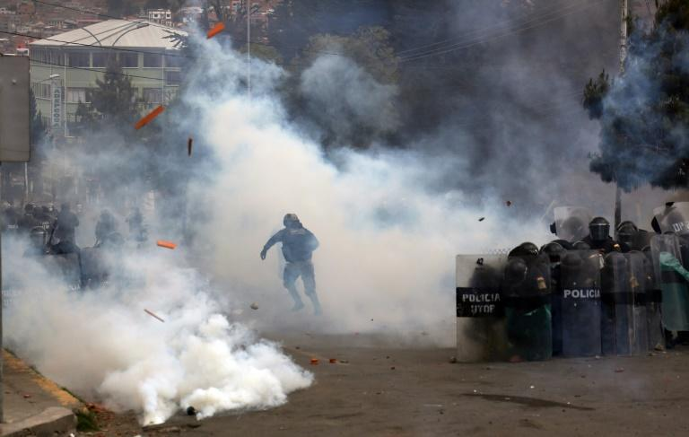 Riot police throw tear gas towards coca leaf producers during clashes outside the coca market in La Paz (AFP/LUIS GANDARILLAS)