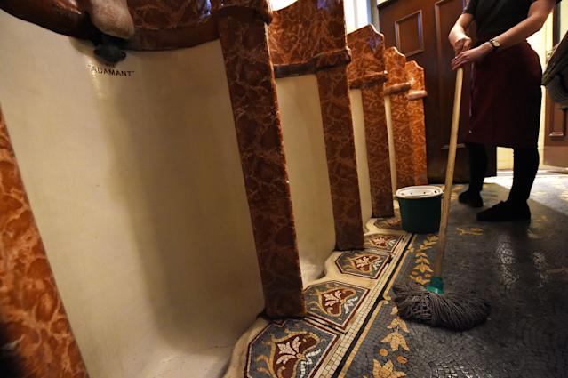 <p>A worker at the ornate men's toilets in the Philharmonic dining rooms in Liverpool, England. (Photo: Paul Ellis/AFP/Getty Images) </p>