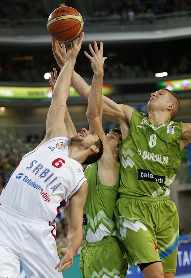 Serbia's Vasilje Micic, left, fights for a rebound with Slovenia's Goran Dragic, center, and Edo Muric during their EuroBasket European Basketball Championship classification 5th to 8th place play off match in Ljubljana, Slovenia, Thursday, Sept. 19, 2013. (AP Photo/Petr David Josek)