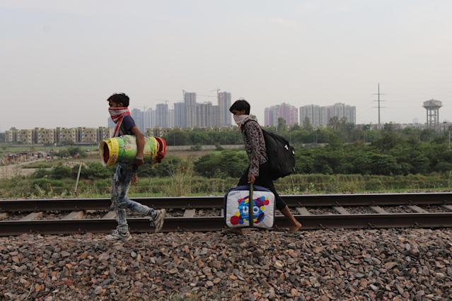 GHAZIABAD, UTTAR PRADESH, INDIA - 2020/05/13: Migrant workers carrying their belongings walk along a railway track returning to their home, during an extended nationwide lockdown to slow the spread of the coronavirus disease. (Photo by Amarjeet Kumar Singh/SOPA Images/LightRocket via Getty Images)