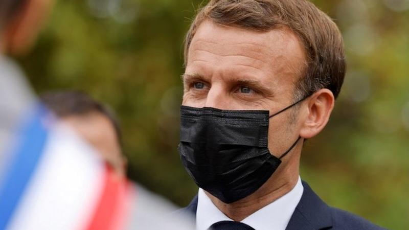 """French President Emmanuel Macron wearing a protective face mask speaks arriving at """"la Maison des habitants"""" (MDH) to meet and have lunch with young representatives of the MDH in Les Mureaux, outside Paris, 2 October 2020"""