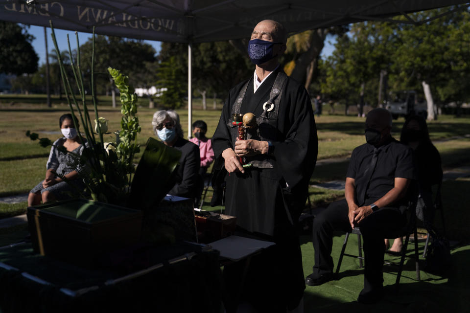 Shumyo Kojima, a head priest of Zenshuji Buddhist Temple, leads a memorial service for Giichi Matsumura at Woodlawn Cemetery in Santa Monica, Calif., Monday, Dec. 21, 2020. Giichi Matsumura, who died in the Sierra Nevada on a fishing trip while he was at the Japanese internment camp at Manzanar, was reburied in the same plot with his wife 75 years later after his remains were unearthed from a mountainside grave. (AP Photo/Jae C. Hong)