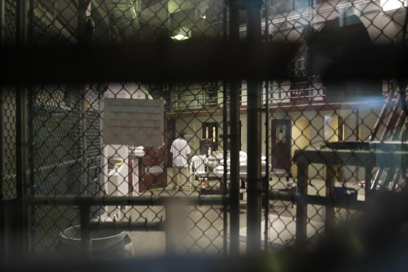 """In this photo reviewed by a U.S. Department of Defense official, a prisoner walks through a communal pod inside an area of the Guantanamo Bay detention center known as Camp 6, an area for prisoners who are considered """"highly compliant"""" with the rules, at Guantanamo Bay Naval Base, Cuba, Saturday, June 7, 2014. (AP Photo/Ben Fox)"""