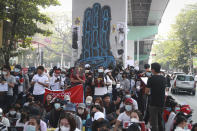 Protesters gather in front of three-fingered salute graffiti during an anti-coup protest in Sanchaung township, outskirt of Yangon, Myanmar, Sunday, Feb. 21, 2021. Police in Myanmar shot dead a few anti-coup protesters and injured several others on Saturday, as security forces increased pressure on popular revolt against the military takeover. (AP Photo)