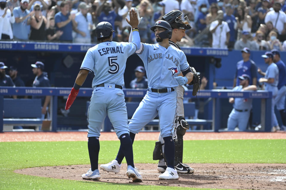 Toronto Blue Jays' Randal Grichuk, right, celebrates his two-run home run with teammate Santiago Espinal in the second inning of a baseball game against the Detroit Tigers in Toronto, Saturday, Aug. 21, 2021. (Jon Blacker/The Canadian Press via AP)