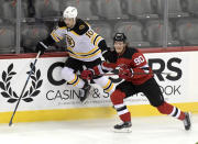 Boston Bruins left wing Anders Bjork (10) attempts to get by New Jersey Devils center Jesper Boqvist (90) during the first period of an NHL hockey game Saturday, Jan. 16, 2021, in Newark, N.J. (AP Photo/Bill Kostroun)