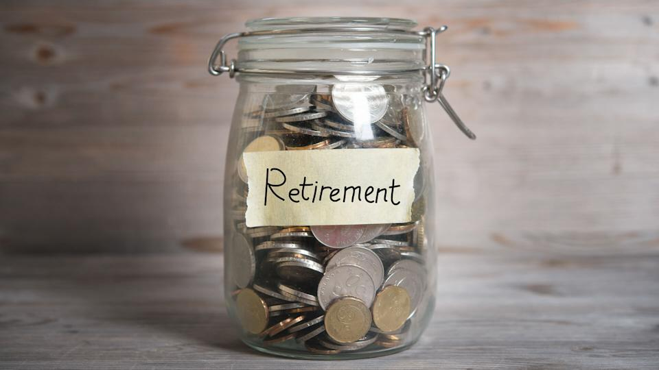 Coins in glass jar with retirement label, financial concept.