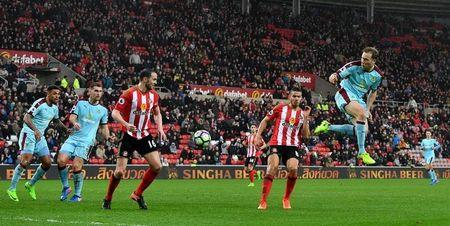 Burnley's Scott Arfield shoots at goal as Sunderland's John O'Shea and Jack Rodwell (2nd R) look on