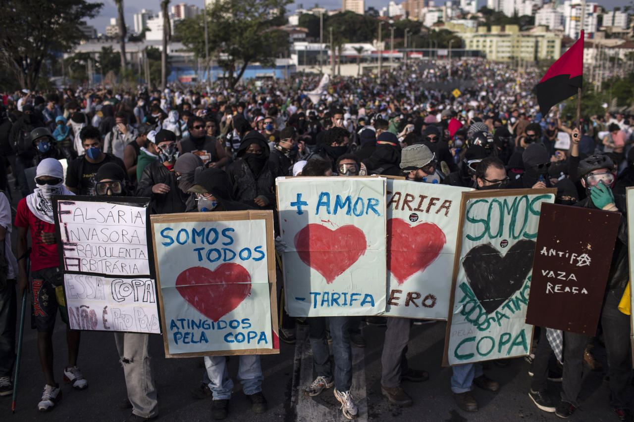 """People use protest signs as shields as they demonstrate outside Minerao stadium where a Confederations Cup soccer match takes place between Japan and Mexico in Belo Horizonte, Brazil, Saturday, June 22, 2013. The sign at center reads in Portuguese """"More love, less fare,"""" referring to the fares for public transportation. Demonstrators once again took to the streets of Brazil on Saturday, continuing a wave of protests that have shaken the nation and pushed the government to promise a crackdown on corruption and greater spending on social services. (AP Photo/Felipe Dana)"""