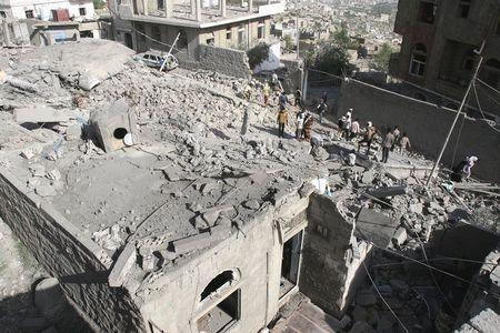 People gather at the site of Saudi-led air strikes in Yemen's central city of Taiz