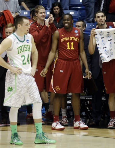 Iowa State guard Nkereuwem Okoro (11) and forward Georges Niang, right, celebrate on the bench while Notre Dame guard Pat Connaughton (24) stands on court at the end of their second-round game at the NCAA college basketball tournament, Friday, March 22, 2013, in Dayton, Ohio. Iowa State won 76-58. (AP Photo/Al Behrman)