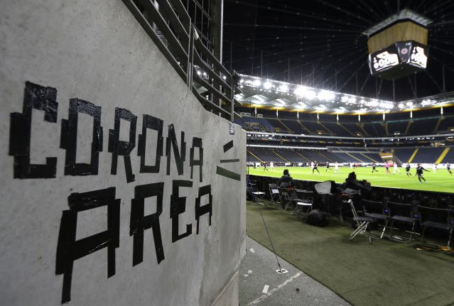 FILE - In this Thursday, March 12, 2020 file photo shows a sign taped by Eintracht fans on a wall of the stadium during a Europa League round of 16, 1st leg soccer match between Eintracht Frankfurt and FC Basel in Frankfurt, Germany. (AP Photo/Michael Probst)