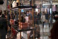 Customers wearing face masks following the coronavirus disease (COVID-19) outbreak, look at the products at a Gucci store, at the Sanya International Duty-Free Shopping Complex, in Sanya