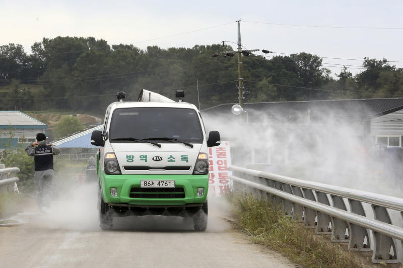 Disinfectant solution is sprayed from a vehicle as a precaution against African swine fever near a pig farm in Paju, South Korea, Friday, Sept. 20, 2019. South Korea said Friday that it is investigating two more suspected cases of African swine fever from farms near its border with North Korea, as fears grow over the spread of the illness that has decimated pig herds across Asia. (AP Photo/Ahn Young-joon)