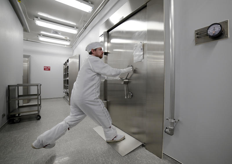 Jeremy Kent, Apollo sample curation processor, tugs to open the 1978 U.S. federal bank vault that protects the entrance to the lunar sample vault inside the lunar lab at the NASA Johnson Space Center Monday, June 17, 2019, in Houston. The door requires two separate combinations, held by two separate people, to open. (AP Photo/Michael Wyke)