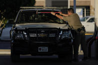 """An officer cleans the windshield of a Department of Public Safety vehicle at a gas station, Wednesday, Sept. 22, 2021, in Del Rio, Texas. The """"amistad,"""" or friendship, that Del Rio, Texas, and Ciudad Acuña, Mexico, celebrate with a festival each year has been important in helping them deal with the challenges from a migrant camp that shut down the border bridge between the two communities for more than a week. Federal officials announced the border crossing would reopen to passenger traffic late Saturday afternoon and to cargo traffic on Monday. (AP Photo/Julio Cortez)"""