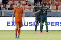 Houston Dynamo midfielder Matias Vera (22) walks off as Portland Timbers Jeremy Ebobisse, middle, and Jose van Rankin (2) celebrate the goal by Ebobisse during the second half of an MLS soccer match Wednesday, June 23, 2021, in Houston. (AP Photo/Michael Wyke)