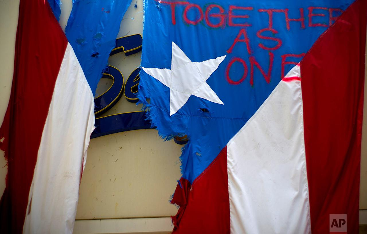 """<p>A damaged Puerto Rican national flag spray painted with the words """"Together as One"""" hangs from the facade of a business, in San Juan, Puerto Rico. The relief effort from Hurricane Maria in Puerto Rico has so far been concentrated largely in San Juan, and many outside the capital say they've received little or no help. (AP Photo/Ramon Espinosa) </p>"""