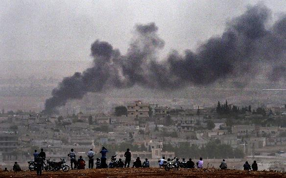 Kurdish people look at smoke rising from the Syrian town of Ain al-Arab, known as Kobane by the Kurds, from Mursitpinar on the Turkish-Syrian border, on October 11, 2014