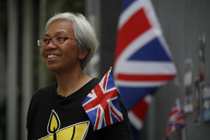 """In this Thursday July 4, 2019, photo, Alexandra Wong, 63, a protester who's often seen raising the Union Jack at demonstrations and carried one into the legislative building on Monday night stands near the flags outside the Central Government Office in Hong Kong. """"I miss the British-Hong Kong government before 1997. The British helped us build a lot of things: separation of powers, our rule of law, our entire social system,"""" said Wong.(AP Photo/Andy Wong)"""