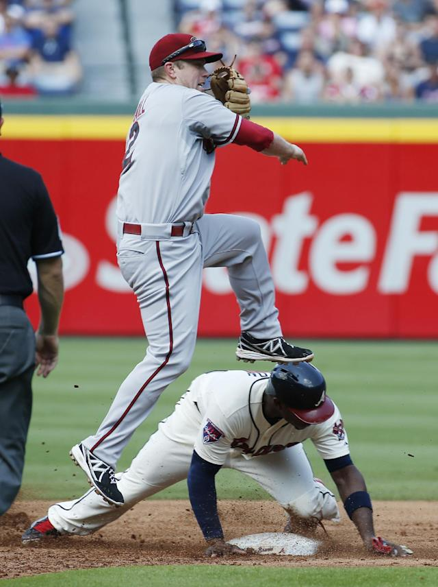 Arizona Diamondbacks second baseman Aaron Hill (2) avoids Atlanta Braves' Justin Upton, bottom, as he tries to turn a double play on a ground ball hit by Braves' Jason Heyward in the second inning of a baseball game in Atlanta, Saturday, July 5, 2014. Heyward was safe at first . (AP Photo/John Bazemore)