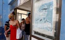 A picture of the former Cuban President Raul Castro is seen as a woman comes out of the local shop in Havana, Cuba July 21, 2018. REUTERS/Stringer