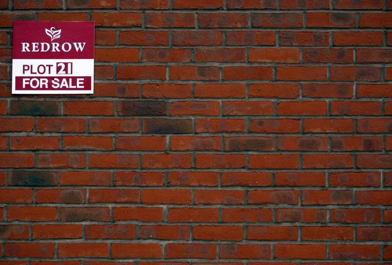 A for sale sign is seen on a house on a Redrow housing development in Church Greasly, central England