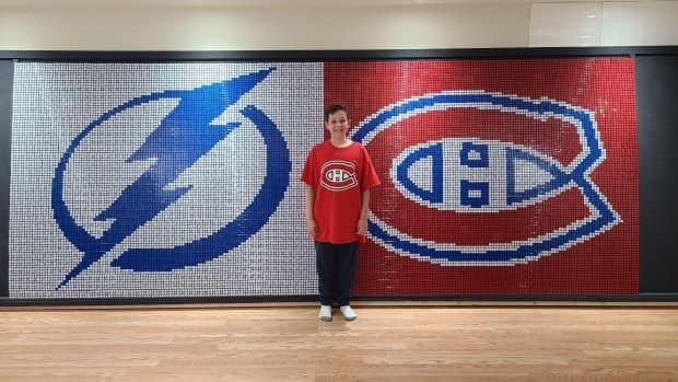 Benjamin Russo, 10, used Rubik's cubes to make a 4.6-by-1.8-metre mosaic of the Habs logo beside the Tampa Bay Lightning's to celebrate the Stanley Cup final.   (Submitted by Melanie Brethour - image credit)