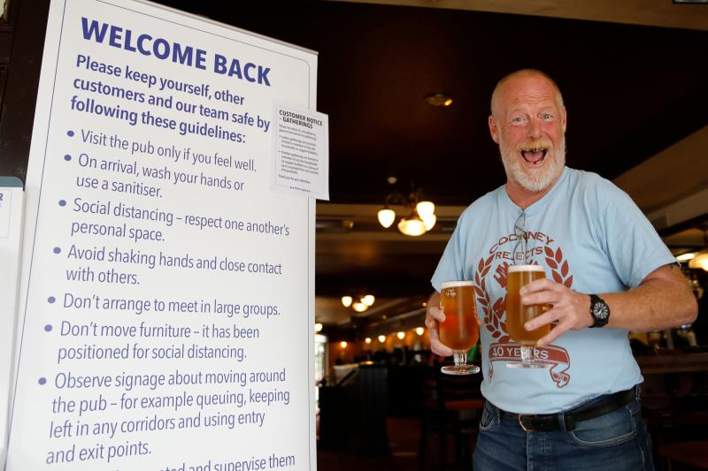 A customer reacts as he walks with two pints of beer past an information board giving advice on new anti-covid measures inside the Wetherspoon pub, Goldengrove in Stratford in east London on July 4, 2020, as restrictions are further eased during the novel coronavirus COVID-19 pandemic. - Pubs in England reopen on Saturday for the first time since late March, bringing cheer to drinkers and the industry but fears of public disorder and fresh coronavirus cases. (Photo by Tolga AKMEN / AFP) (Photo by TOLGA AKMEN/AFP via Getty Images)
