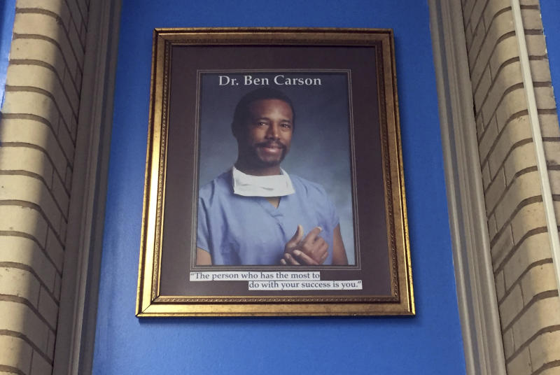 In this May 3, 2018, photo, a portrait of Ben Carson hangs in the Ben Carson Reading Room inside of the Archbishop Borders School in Baltimore. The portrait used to hang in the school's hallway, but Principal Alicia Freeman moved it out of public view during Carson's presidential campaign. Carson's story of growing up in a single-parent household and climbing out of poverty to become a world-renowned surgeon was once ubiquitous in Baltimore, where Carson made his name. But his role in the Trump Administration has added a complicated epilogue, leaving many who admired him feeling betrayed, unable to separate him from the politics of a president widely rejected by African Americans here. (AP Photo/Juliet Linderman)