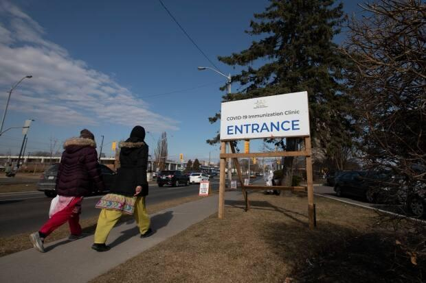 Toronto residents walk to a COVID-19 mass vaccination clinic at the East York Town Centre mall in the city's Thorncliffe Park neighbourhood on March 24, 2021.