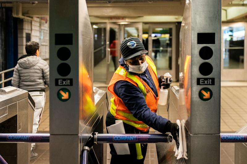 An MTA transit worker cleans a nearly empty Times Square - 42nd street subway station following the outbreak of coronavirus disease (COVID-19), in New York City, U.S., March 16, 2020. REUTERS/Jeenah Moon