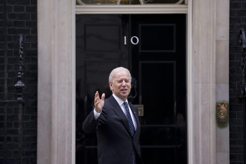 U.S. Vice President Joe Biden waves at members of the media as he arrives to meet British Prime Minister David Cameron at 10 Downing Street in London, Tuesday, Feb. 5, 2013.  Biden will meet with Cameron on Tuesday and attend a meeting of the UK National Security Council on the final leg of his European trip.  (AP Photo/Matt Dunham)