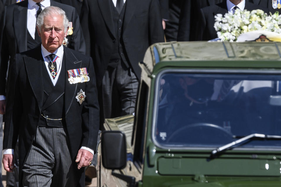 Britain's Prince Charles follows the coffin as it makes it's way past the Round Tower during the funeral of Britain's Prince Philip inside Windsor Castle in Windsor, England Saturday April 17, 2021. (Leon Neal/Pool via AP)